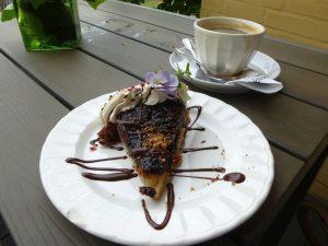 Das Foto zeigt einen Teller mit einem Stück Torte und daneben eine Kaffeetasse. Das Foto ist von Lisa K. Schuermann